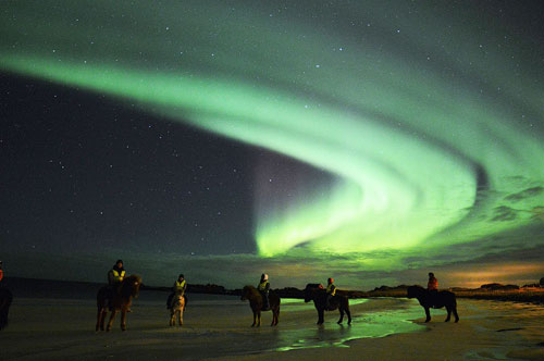 Riding on the beach under Northern Lights
