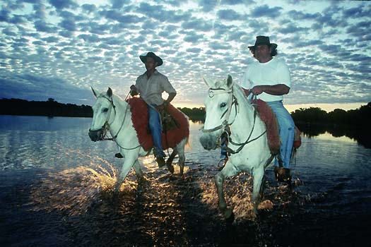 Riders at sunset in the Pantanal, Brazil