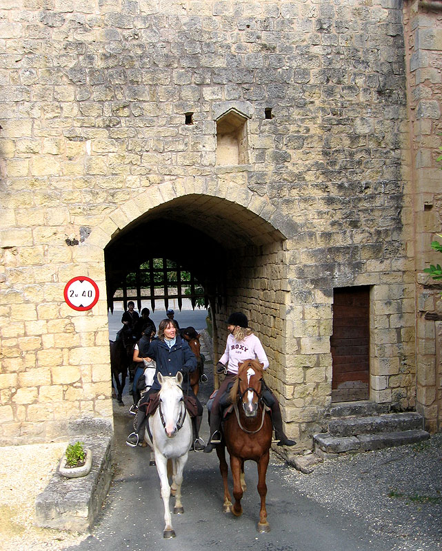 Riding through a porticullus into a fortified village
