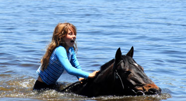 Child swimming with horse on holiday